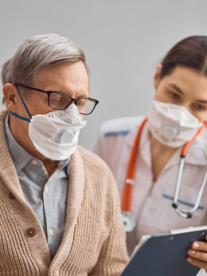 Anciano y doctora usando mascarillas